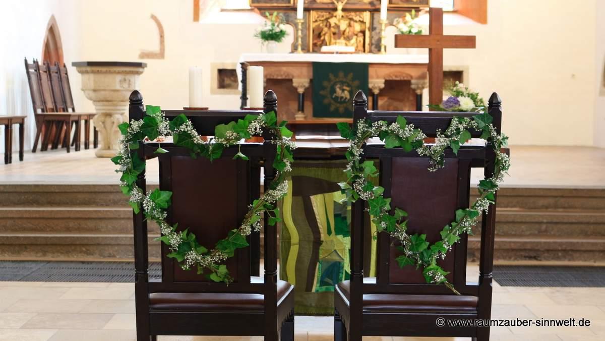 die Stühle fürs Hochzeitspaar mit Efeuherzen und Schleierkraut