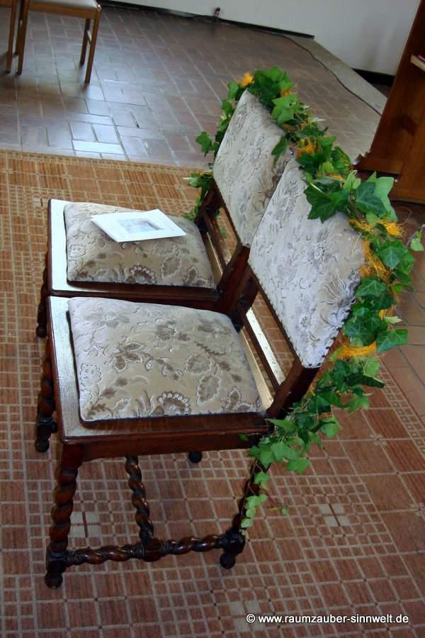 die Stühle fürs Hochzeitspaar mit Efeu und Bändern