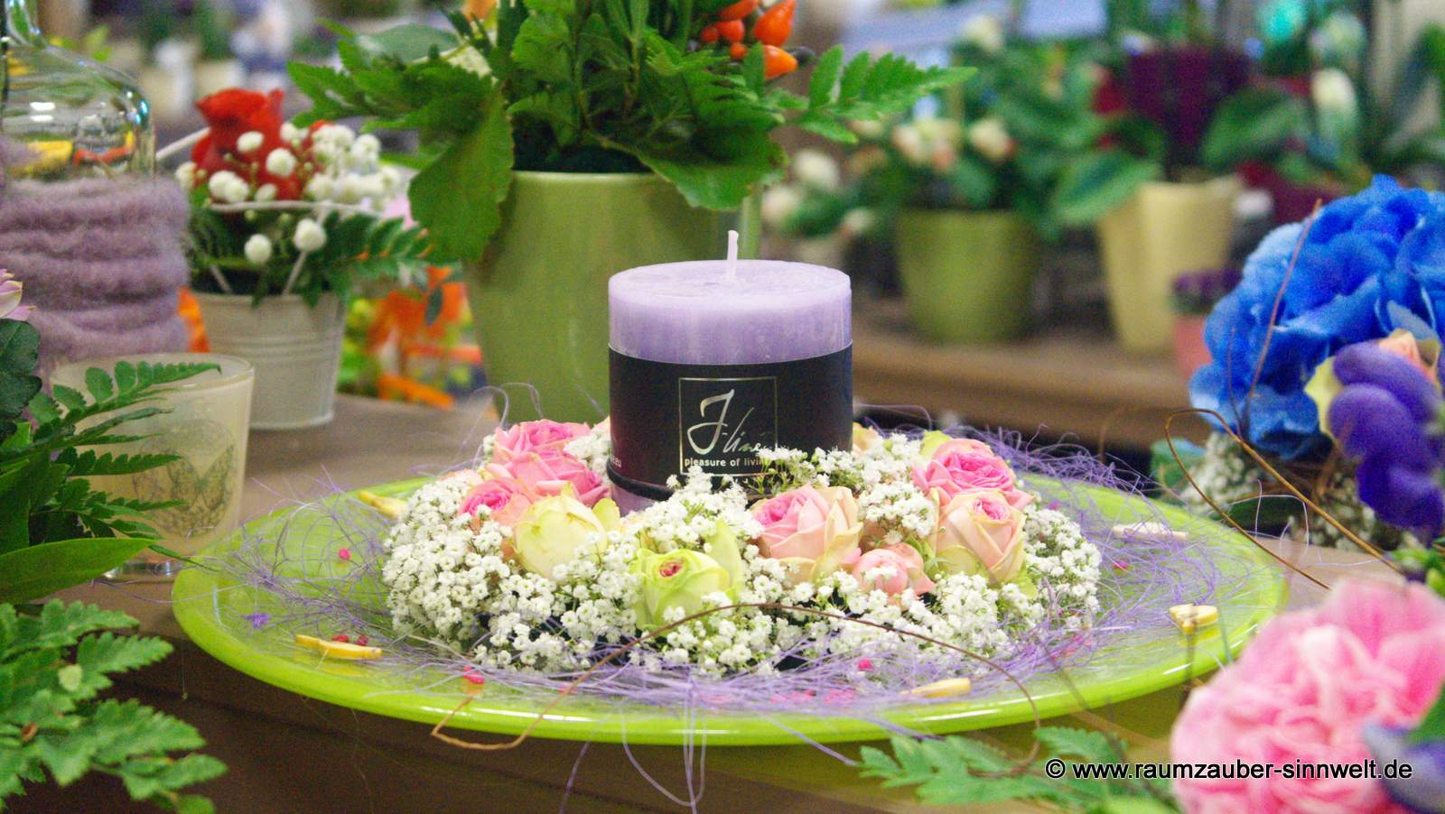 Blumengesteck mit Rosen und Kerze