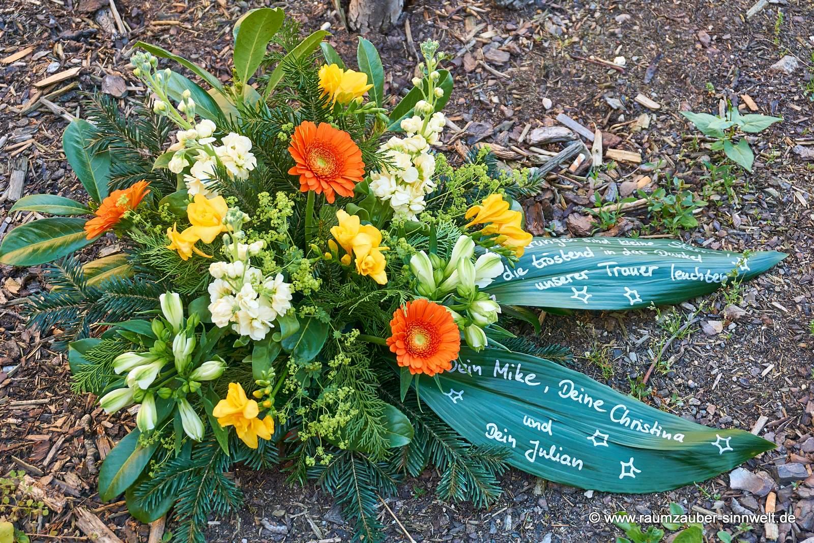 buntes Trauergesteck mit handbeschriebenen Blättern