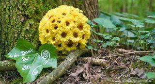 Blütenkugel für den Friedwald aus Chrysanthemen mit beschriebenem Blatt.