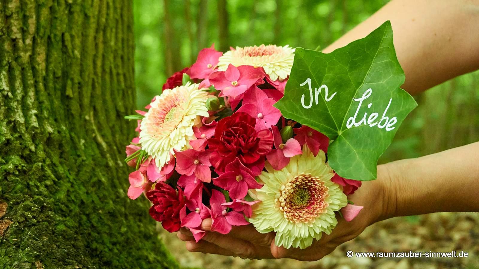Blütenkugel für den Friedwald aus Hortensien und Gerbera mit beschriebenem Blatt.