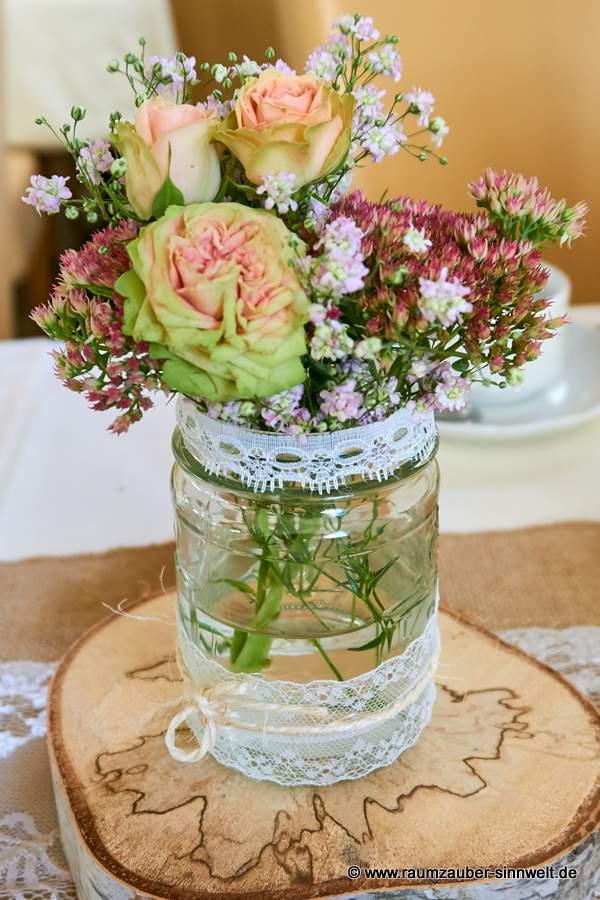 Tischdekoration mit Rosen, Sedum und Schleierkraut