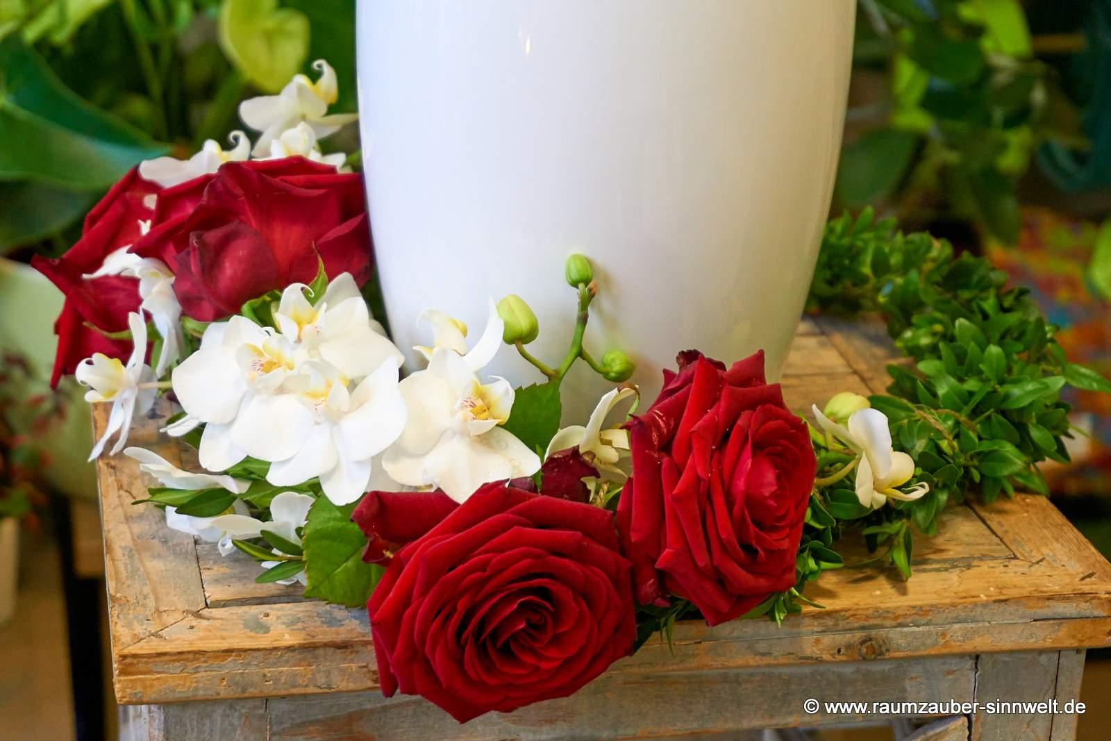 Trauerkranz für den Friedwald aus roten Rosen und weißen Orchideen, nur mit Faden gebunden
