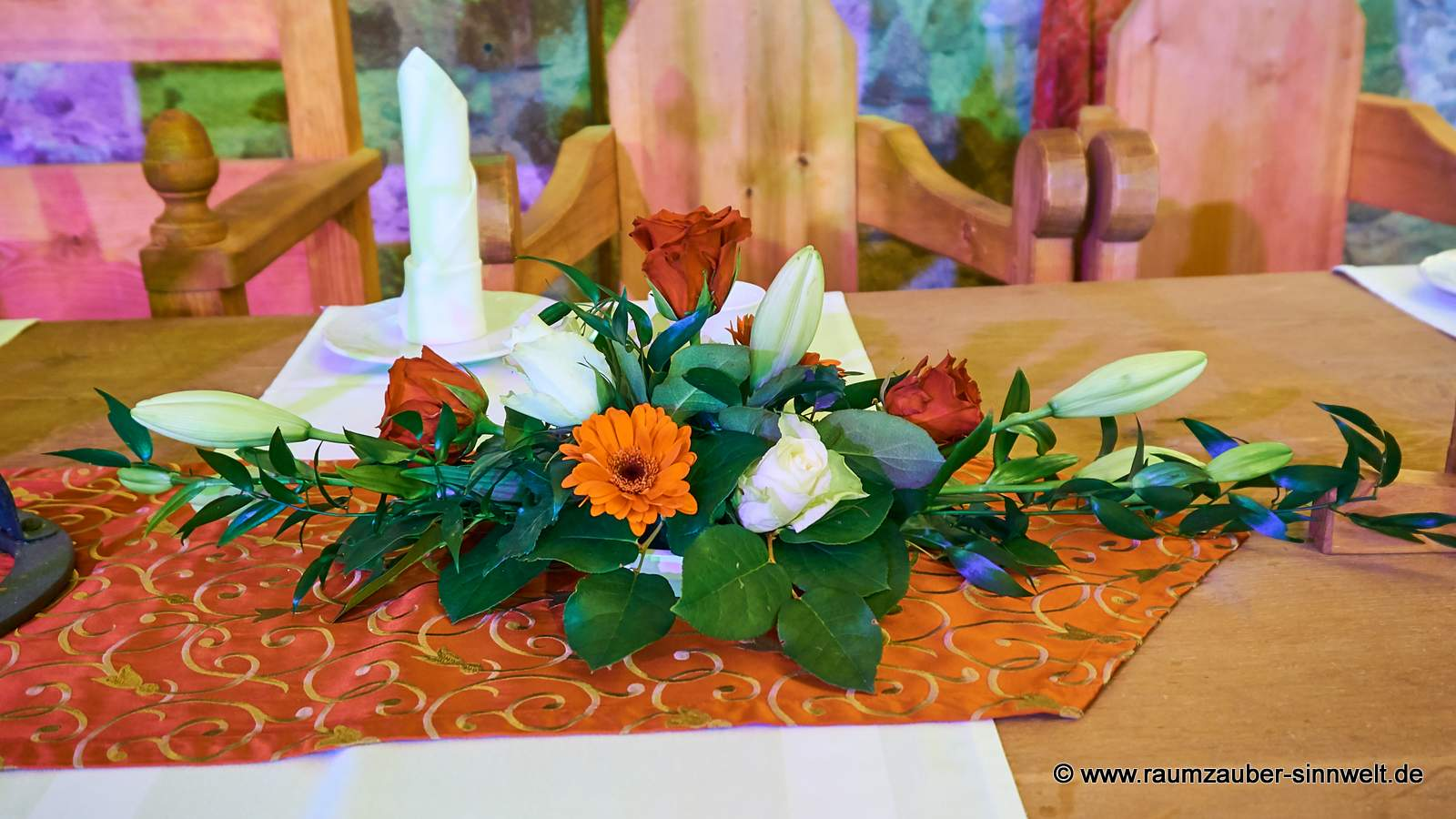 Tischdekoration mit Lilien, Rosen und Gerbera