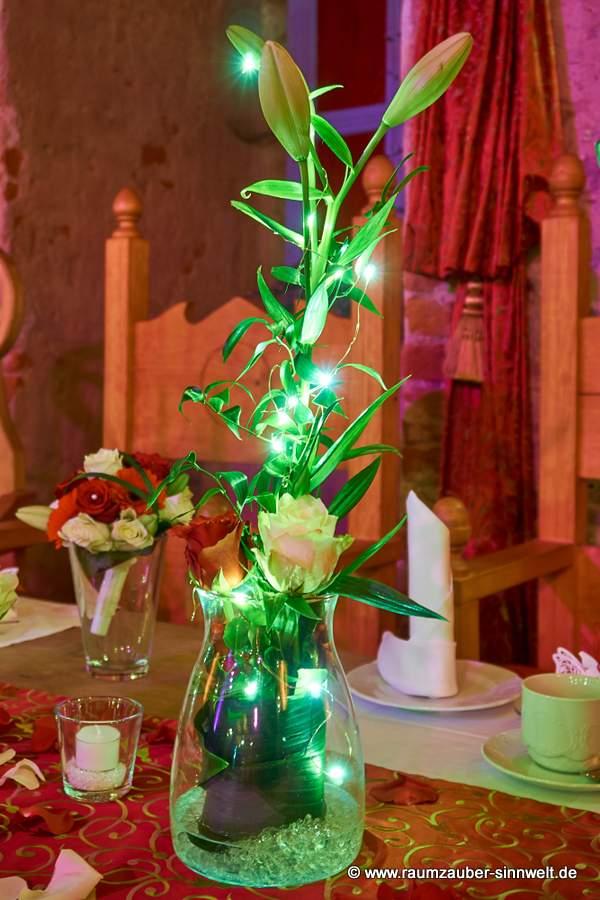 Tischdekoration mit Lilien, Rosen und Gerbera eingehüllt in romantisches Licht.