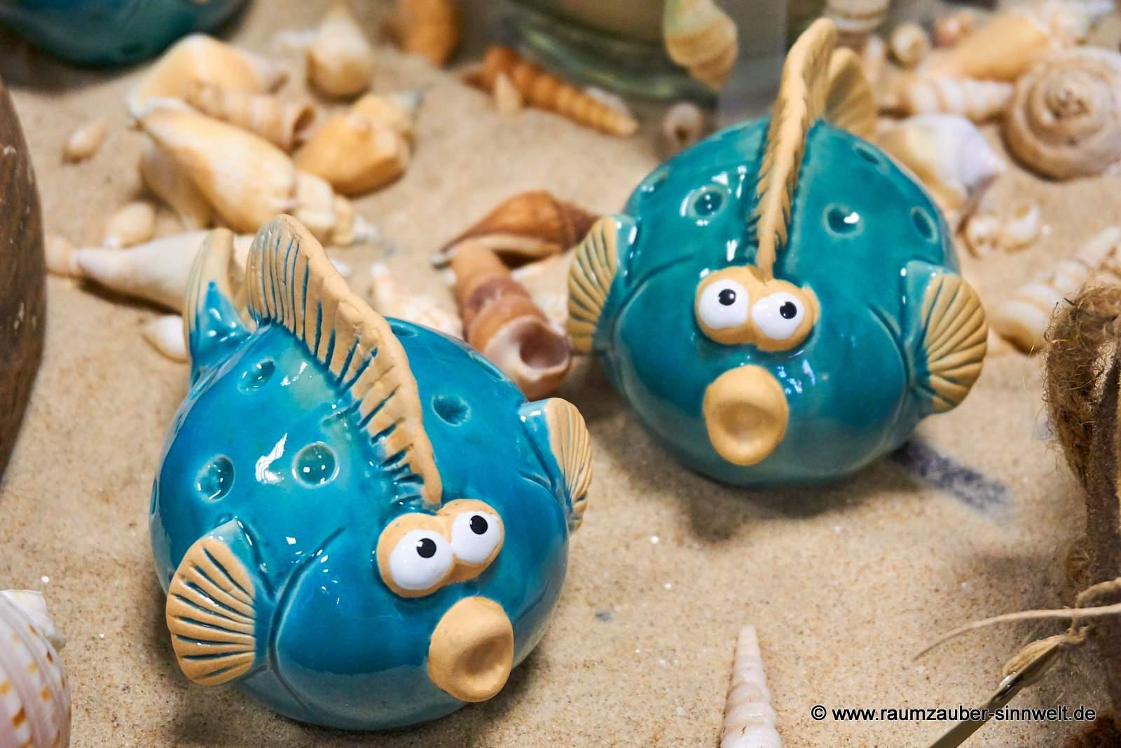 Keramik-Fische mit Sand und Muscheln dekoriert