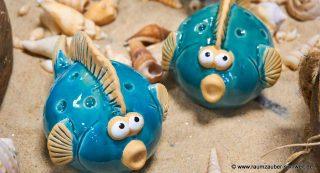 Keramik-Fische sommerlich mit Sand und Muscheln dekoriert