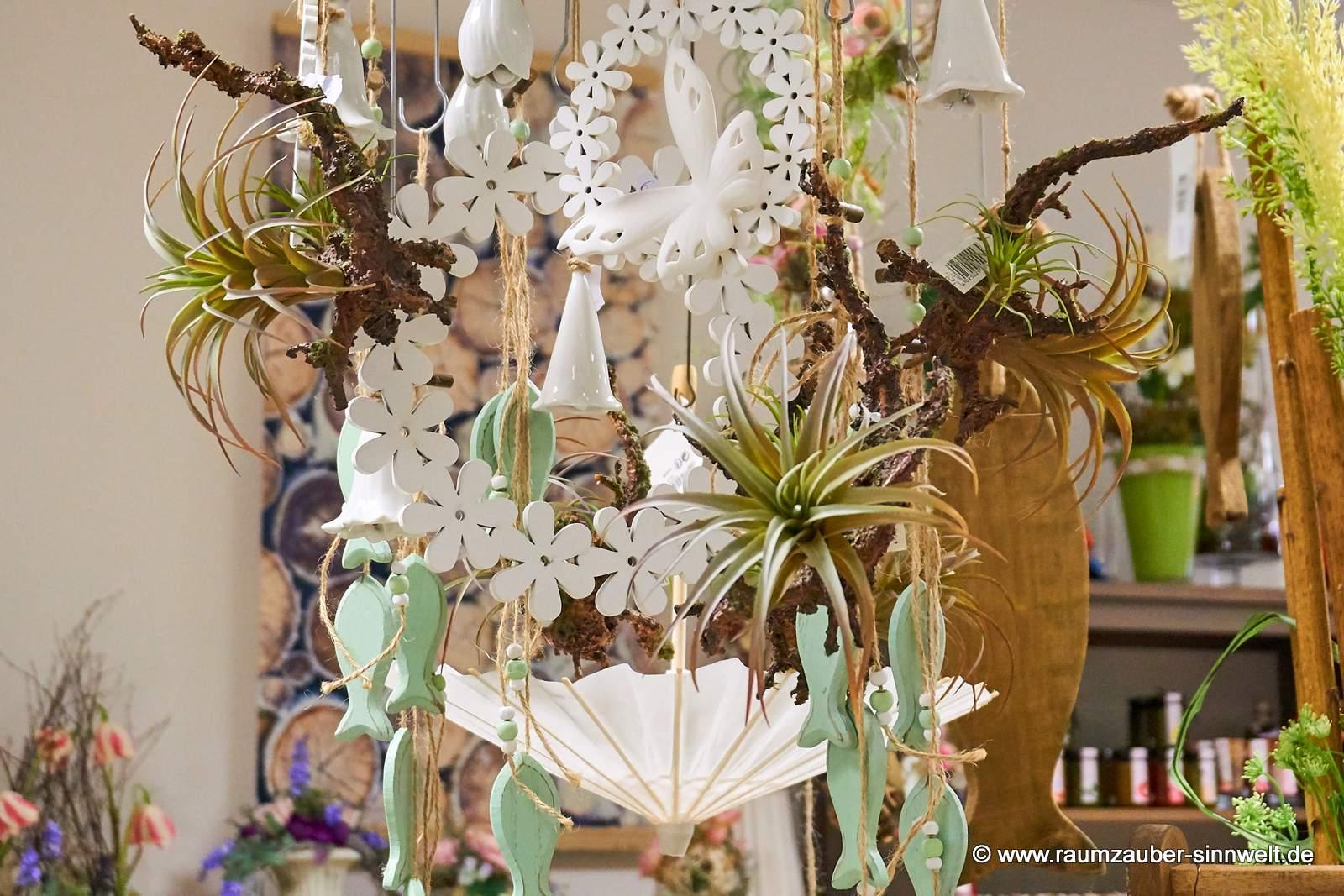 Hänge-Dekoration mit Holzfischen, Blütenkränzen und Tillandsien