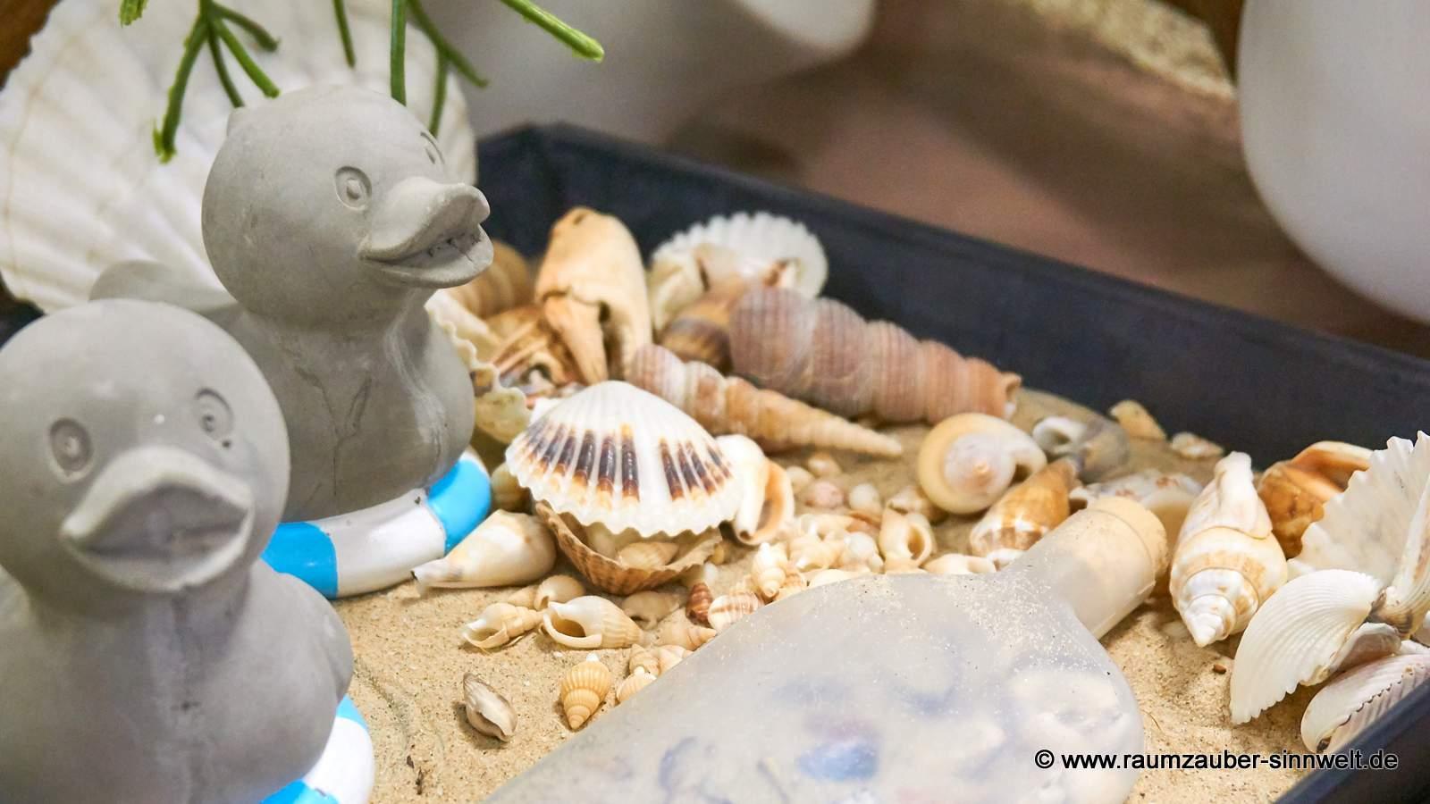 Zement-Enten mit Sand und Muscheln dekoriert