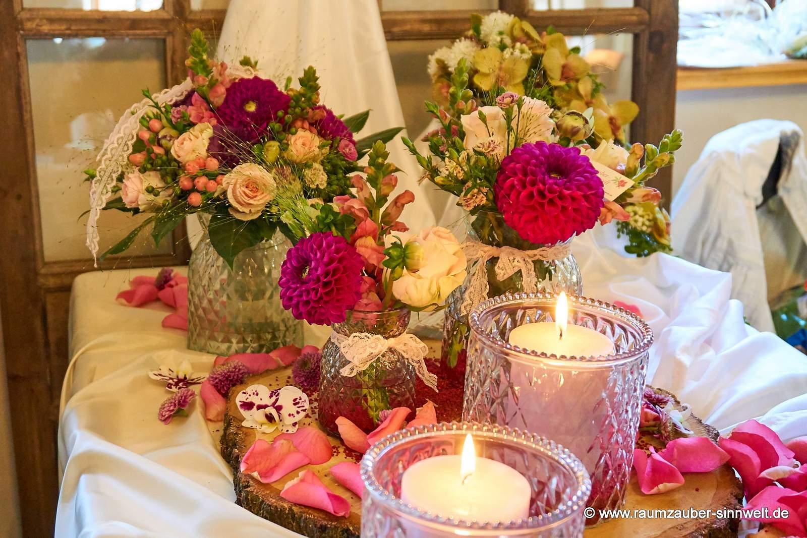 Tischdekoration aus Rosen, Dahlien und Löwenmaul mit Kerzen auf einer Baumscheibe arrangiert.