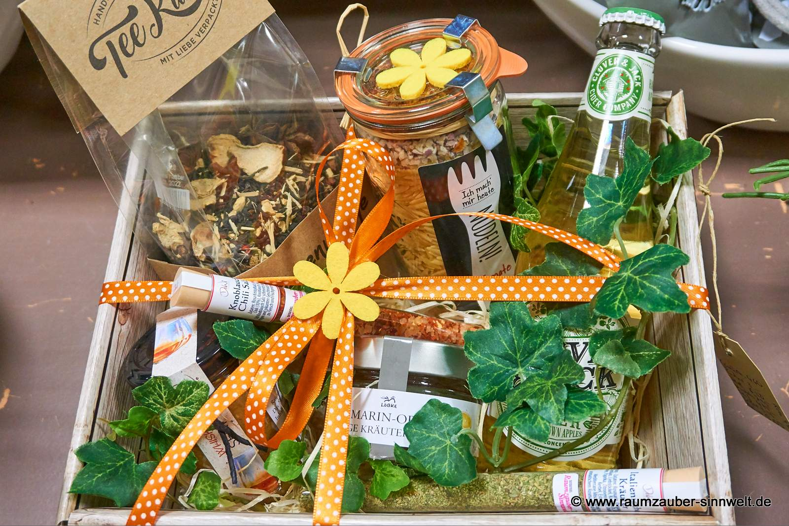 dekorierter Präsentkorb mit Nudeln, Gewürzröhrchen, Senf, Kräutergelee, Kräutertee und Cider
