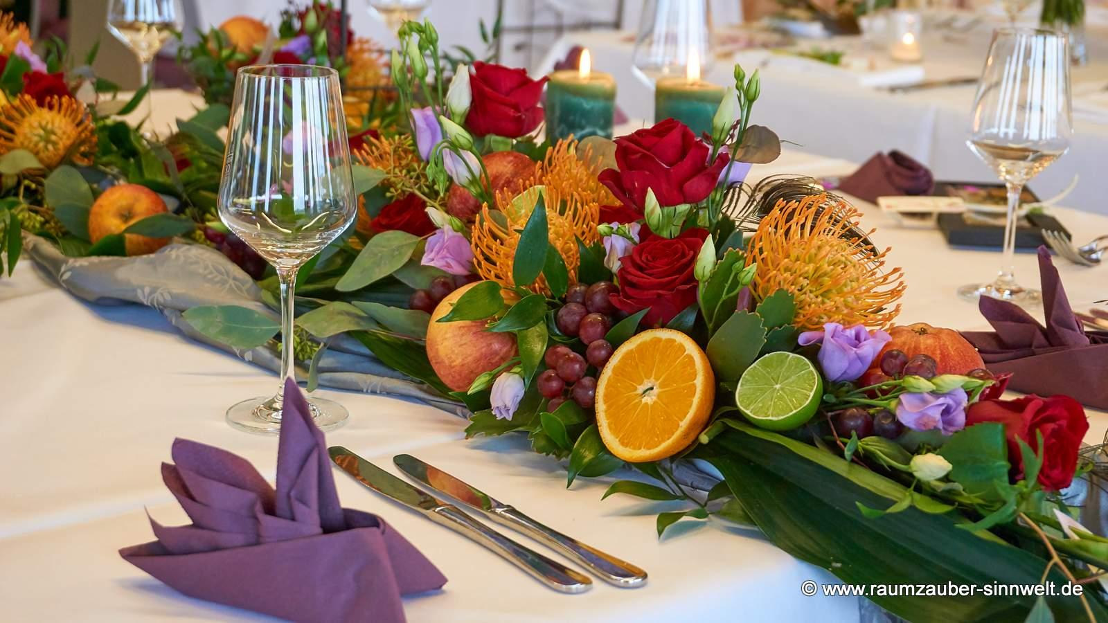 Tischschmuck mit exotischen Blüten und Früchten